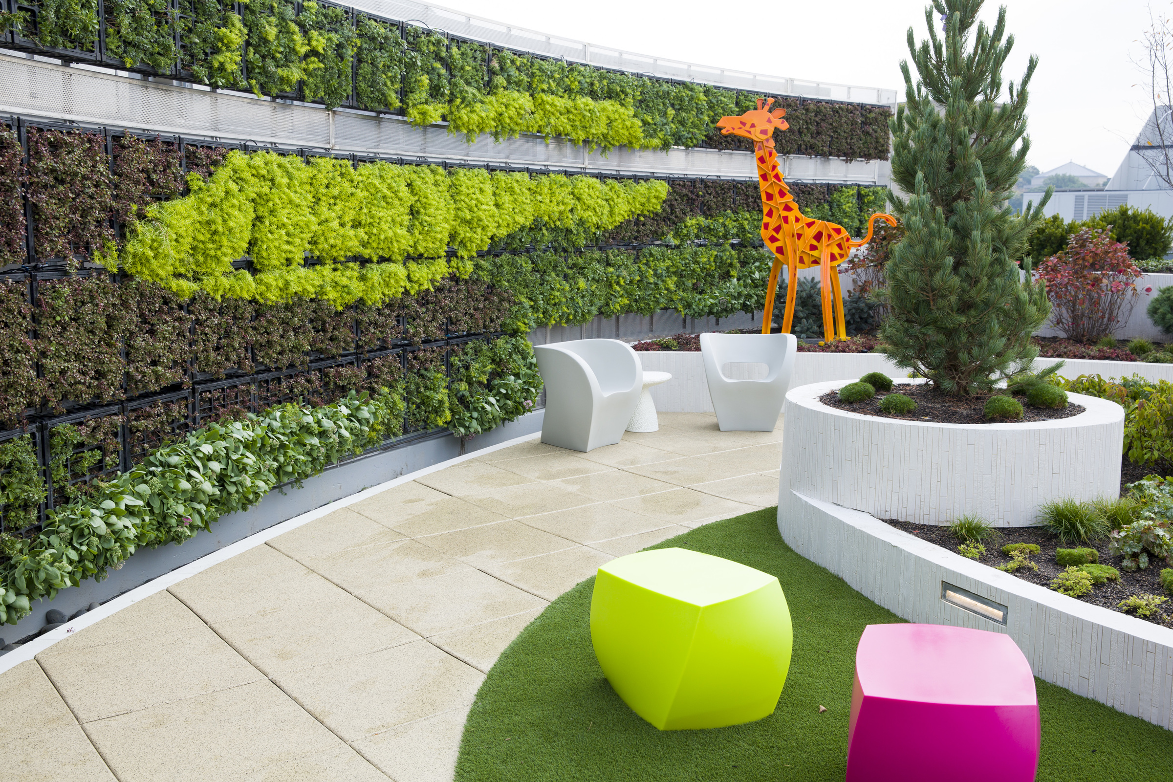 a rooftop garden with bright colors and a large decorative giraffe