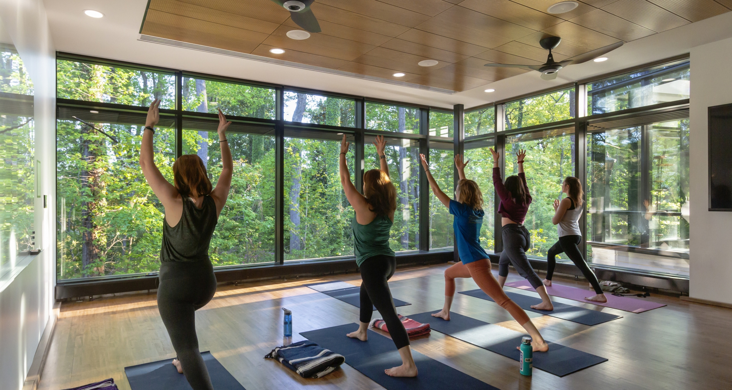 Students practice yoga in a window filled studio at The College of William & Mary