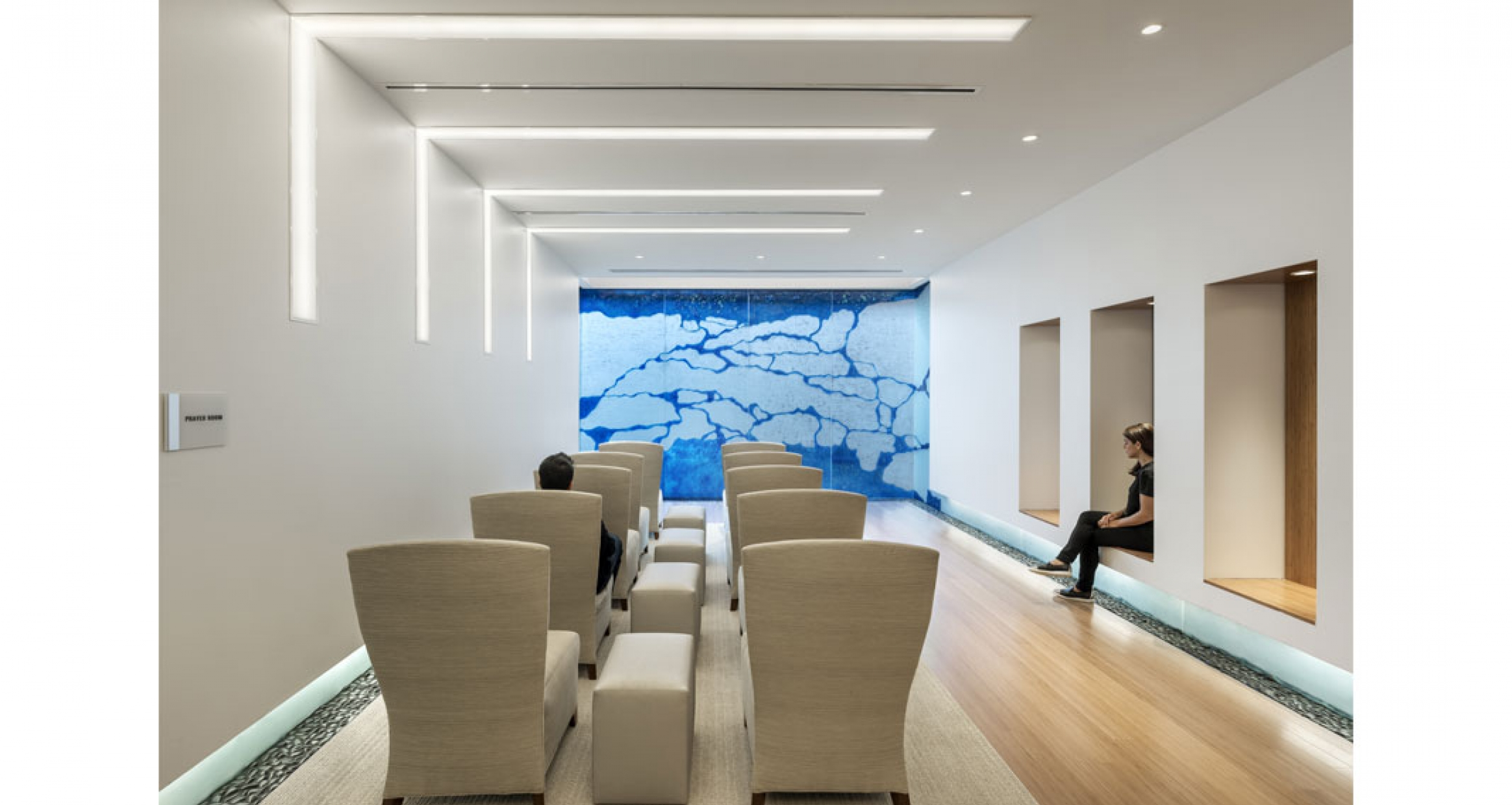The chapel's features glass art wall by Gordon Huether features radiant blue details, reminiscent of gently flowing water in a creek, evoking a sense of peace and calmness, conveying an uplifting sense of healing and well-being.